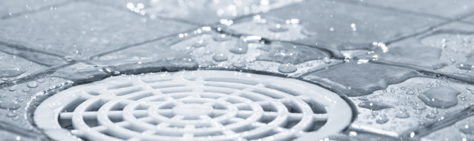 Where should the drain be placed in a shower?